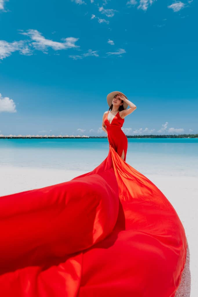 Red flying dress on a beach photoshoot